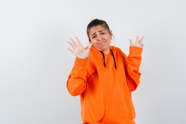 Женщина в оранжевой толстовке с капюшоном показывает ладони в жесте капитуляции и выглядит смущенной
