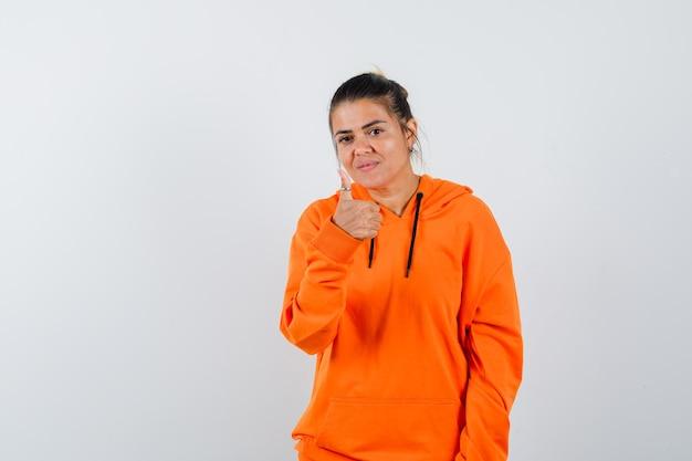 엄지손가락을 치켜세우고 자신감을 보이는 주황색 까마귀를 입은 여성
