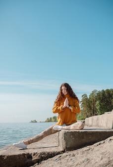 오렌지 스웨터 해변에 돌 계단에 앉아있는 여자