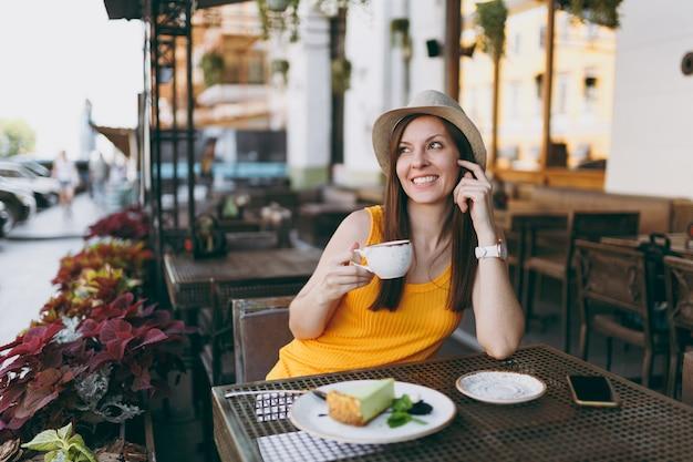 カプチーノ、ケーキ、自由時間のレストランでリラックスして黄色い服の帽子のテーブルに座っている屋外通りのコーヒーショップカフェの女性