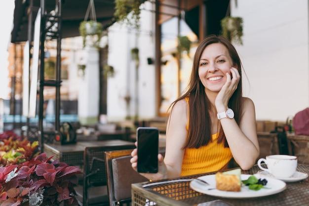 차, 케이크 한잔과 함께 테이블에 앉아 야외 거리 커피 숍 카페에서 여자 빈 빈 화면이 손에 휴대 전화를 개최