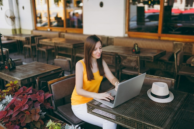 現代のラップトップpcコンピューターで作業しているテーブルに座って、自由時間中にレストランでリラックスして、屋外ストリートコーヒーショップカフェの女性