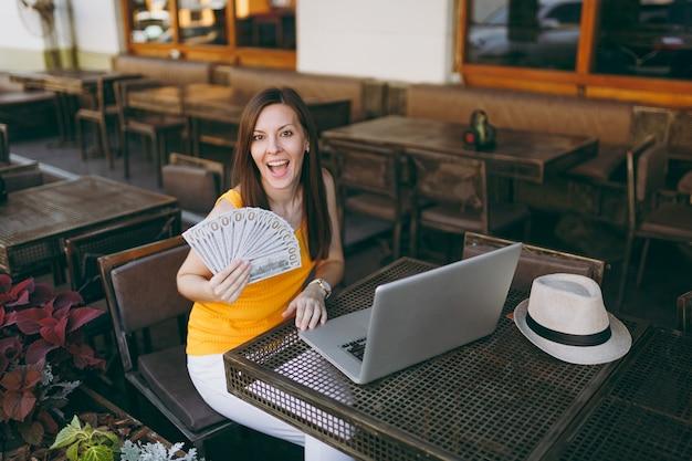Женщина в уличном кафе на открытом воздухе сидит с современным портативным компьютером, держит в руке кучу долларовых банкнот