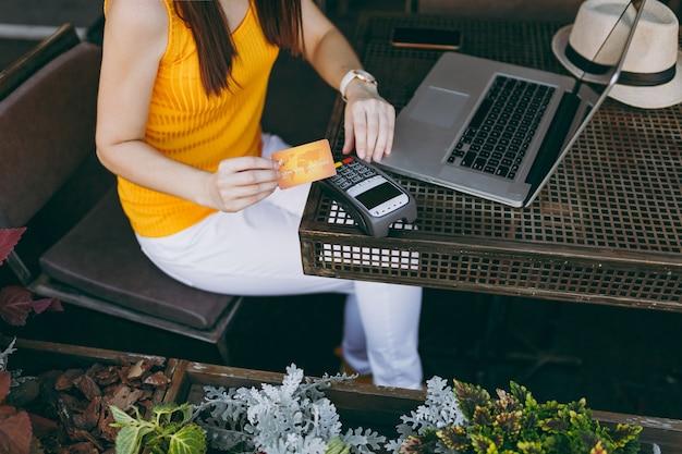 노트북 pc 컴퓨터와 함께 앉아 야외 거리 커피 숍에서 여자는 신용 카드 결제를 처리하기 위해 무선 현대 은행 결제 단말기를 보유하고