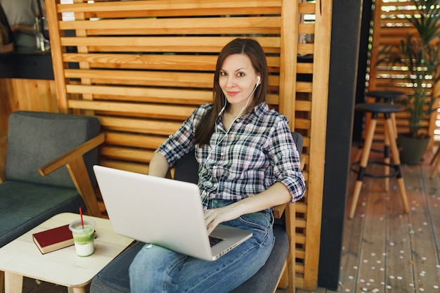 カジュアルな服に座って、現代のラップトップpcコンピューターで作業している屋外通り夏のコーヒーショップ木製カフェの女性