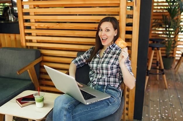 Женщина в уличном летнем кафе в деревянном кафе сидит, работает на портативном компьютере, держит банковскую кредитную карту, расслабляясь в свободное время