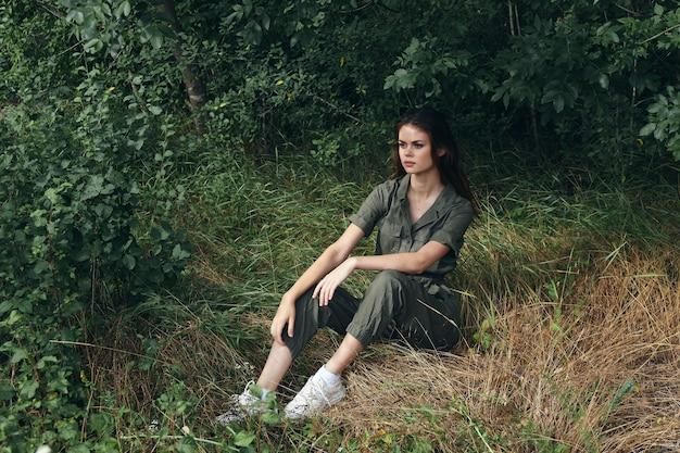 オーバーオールとスニーカーの女性が森のモデルの草の上に座っています