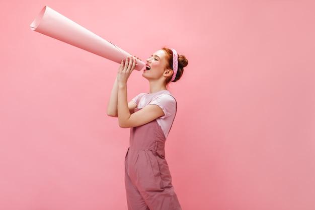 Женщина в комбинезоне кричит в рог и смотрит в камеру на розовом фоне.