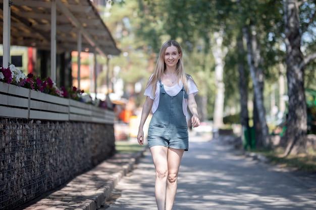 바지를 입은 여자가 여름에 길거리에서 산책