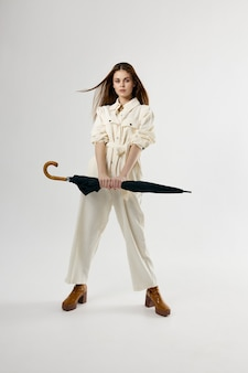 手に傘を持ったオーバーオールの女性完全成長スタジオライフスタイル