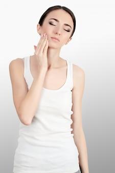 Женщина в боли. крупный план красивой молодой женщины чувствуя болезненную зубную боль, касаясь стороне с рукой. грустно подчеркнутая девушка чувствует сильную боль в зубах, челюсти или шее. стоматологическое здоровье и уход.