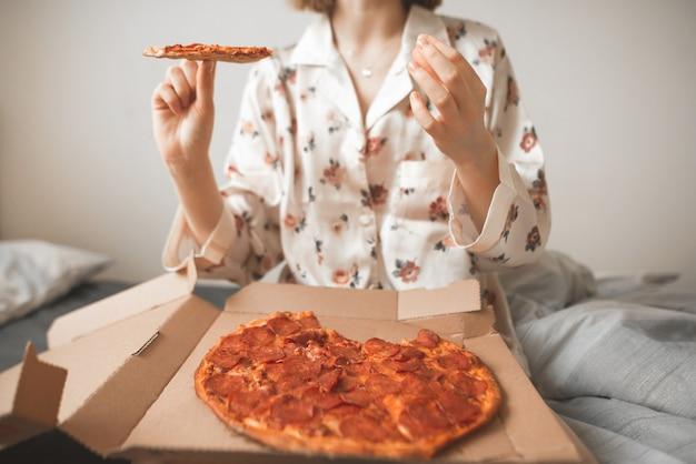 パジャマの女性は、ベッドの上の箱からピザを食べます。