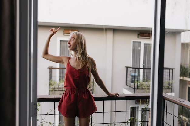 파자마 발코니에 서서 둘러보고있는 여자. 아침을 즐기는 긴 금발 머리를 가진 흥분된 여성 모델.
