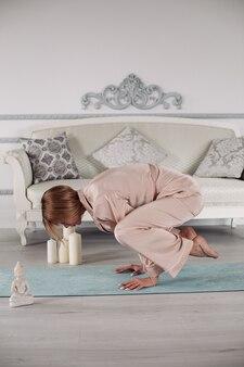아파트 거실에서 요가 운동을 하는 잠옷을 입은 여성이 매트에 손을 기대고 있습니다. 건강한 라이프 스타일 개념입니다. 아침 피트니스