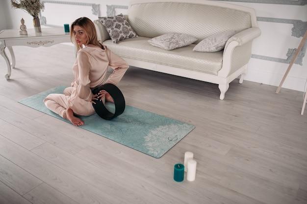 Женщина в пижаме сидит на коврике и делает прогиб во время тренировки утром дома. концепция здорового образа жизни. утренний фитнес