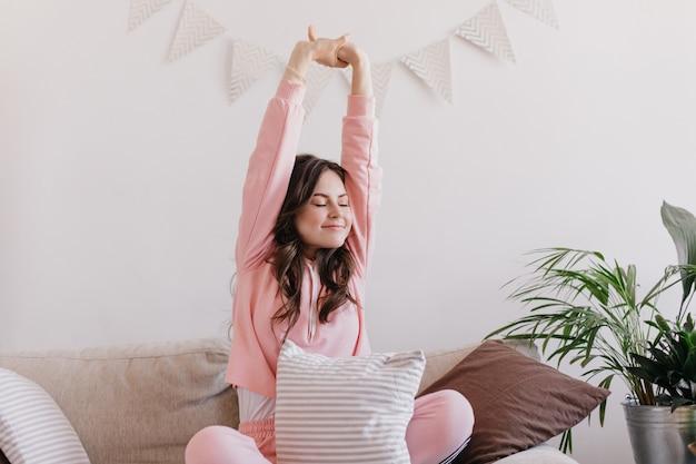 ソファでストレッチパジャマを着た女性