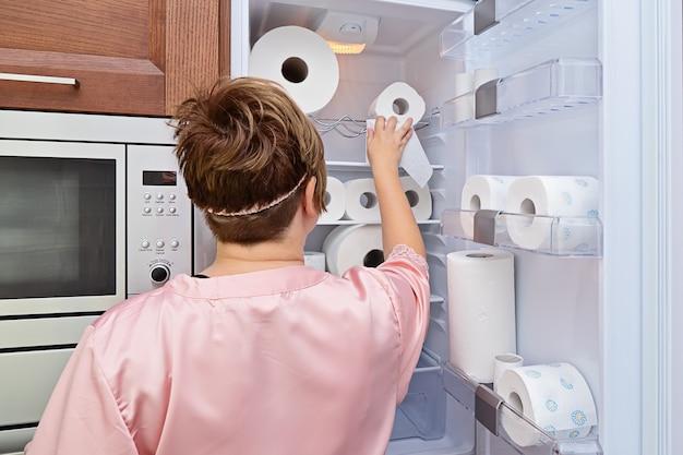 Женщина в пижаме берет из холодильника рулон туалетной бумаги