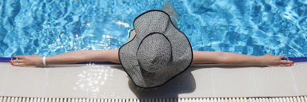 Женщина в панаме лежит в бассейне, широко расставив руки, вид сверху