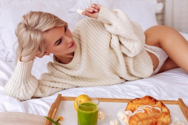 パンティーの女性。ベッドで朝食をとっている白いパンティーを身に着けている短い髪のカットのセクシーなスリムな女性