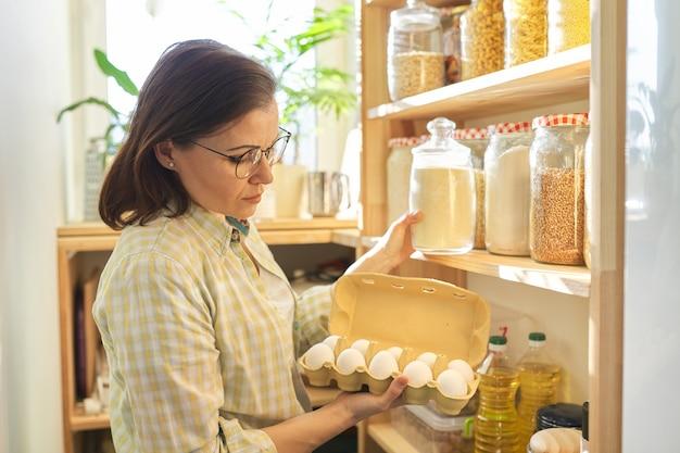 식료품 저장실 복용 제품, 계란에 여자입니다. 식품 저장, 집에서 요리, 저장 용기에 곡물 제품이 담긴 나무 선반