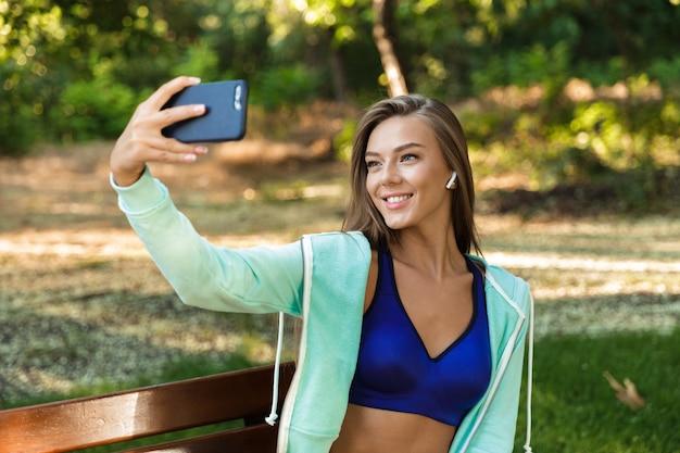 イヤホンで音楽を聴いている屋外の公園の女性は、携帯電話で自分撮りをします。