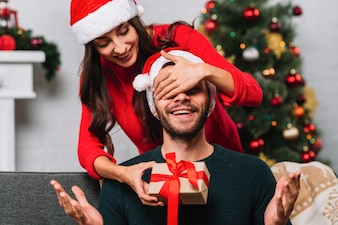 Woman in party hat closing eyes tosurprised man