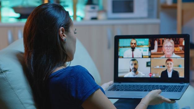 チームとのビデオ会議で販売レポートについて話しているラップトップを使用してソファに横たわっているパジャマの女性。ビデオ通話とウェブカメラチャットを使用して同僚とオンライン会議の相談をしているリモートワーカー