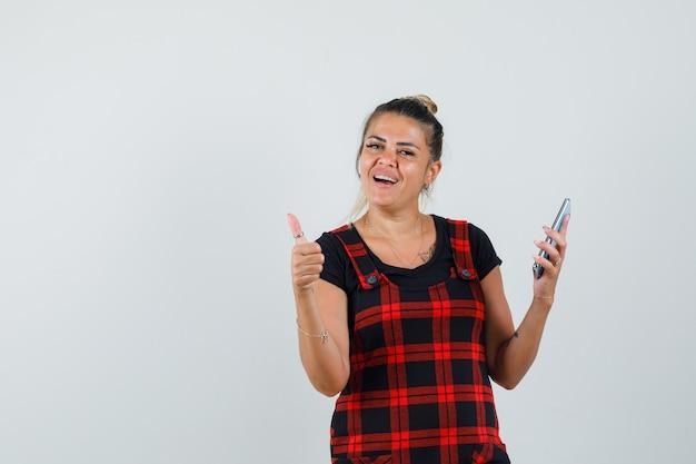 Женщина в платье-сарафане, держащем мобильный телефон, показывая большой палец вверх и уверенно глядя, вид спереди.