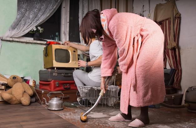 ピンクのバスローブを着た女性が、パートナーが後ろで忙しく掃除している間に、散らかった放棄された部屋の床を磨いています。