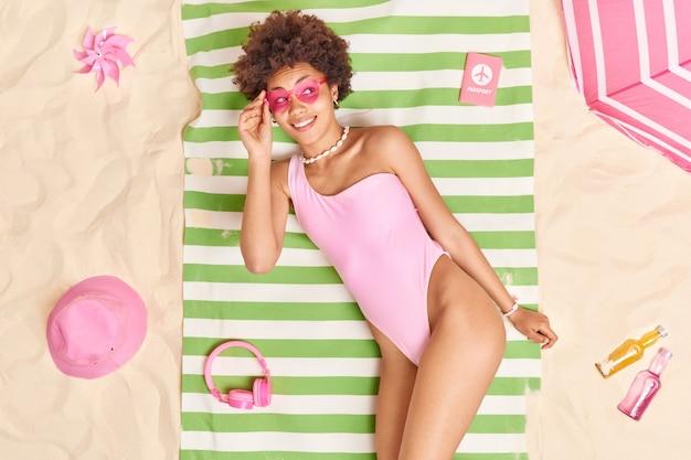 ピンクのビキニのハート型サングラスをかけた女性が、さまざまなものに囲まれた砂浜でタオルの上にポーズをとって、笑顔が幸せに集中します。夏の時間と休息の概念