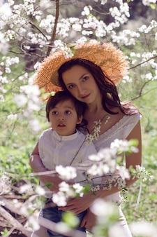 ピンクの服と麦わら帽子の女性は、開花リンゴ園で白いシャツを着た子供と一緒に立っています