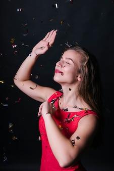 Женщина в розовом платье, танцующая под блестящими блестками