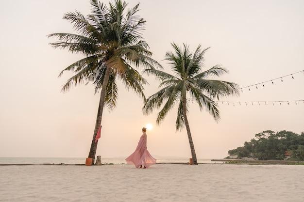 해변에서 아름 다운 석양을 즐기는 핑크 드레스 여자