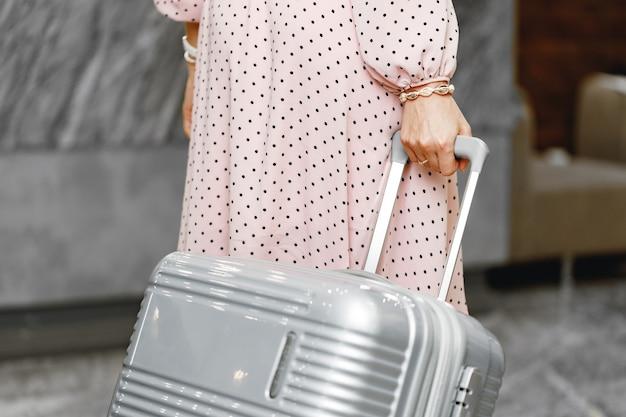 Женщина в розовом платье стоит с чемоданом для багажа