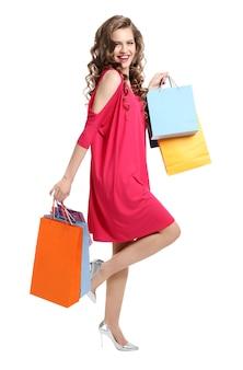 Женщина в розовом платье с хозяйственными сумками на белом фоне