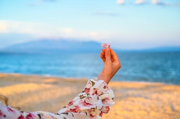 海と山の上の貝殻を保持しているピンクの花のドレスの女性