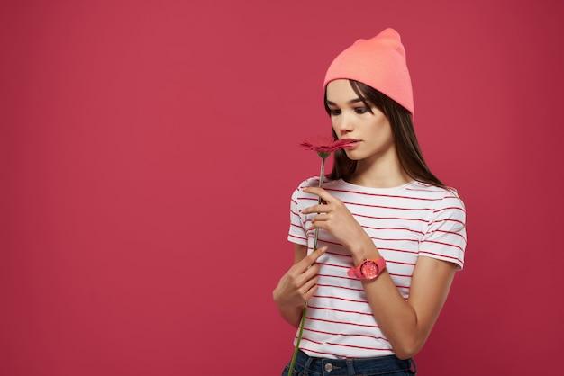 ピンクの帽子の赤い花のロマンスポーズモデルの女性