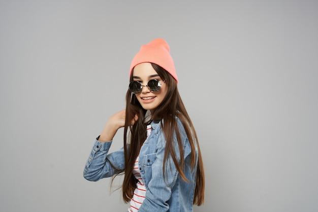 長い髪のファッションをポーズするピンクの帽子のサングラスの女性