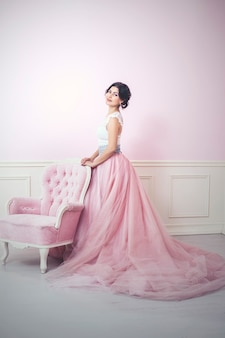 핑크 인테리어의 여자와 공주처럼 핑크색 긴 드레스