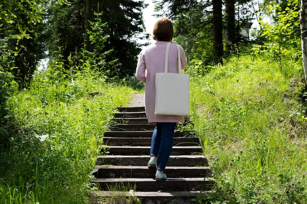 Женщина в розовой куртке, несущей пустой макет многоразовой хозяйственной сумки.