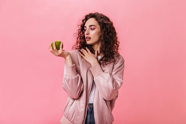 ピンクのジャケットの女性は、孤立した背景でアップルを見て