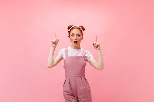 ピンクのジャンプスーツの女性がアイデアを得ました。ピンクの背景に若い赤毛の女性の肖像画。
