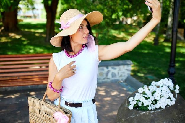 公園のピンクの医療マスクの女性は携帯電話で自分撮りを取ります、呼吸保護の女性はスマートフォンでウェブカメラで話したりビデオチャットしたりしながら屋外にいます