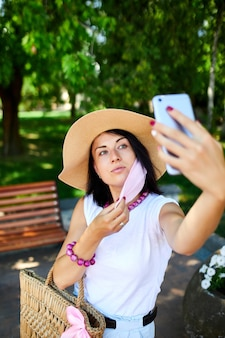 Женщина в розовой медицинской маске в парке делает селфи по мобильному телефону, женщина с защитой органов дыхания находится на улице во время разговора и видеочата с помощью веб-камеры на смартфоне