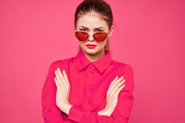 ピンクのシャツと茶色のメガネの女性は、手の肖像画を身振りで示すファッションモデルの感情をクロップドビュー