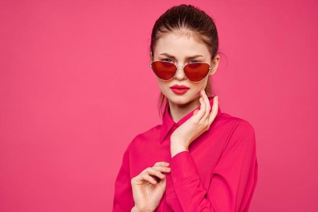ピンクのシャツと茶色のメガネの女性は、ビューをトリミングしました。