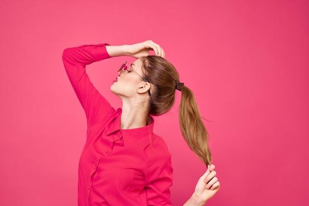 ピンクのシャツと茶色のメガネの女性、手の肖像画を身振りで示すファッションモデルの感情。