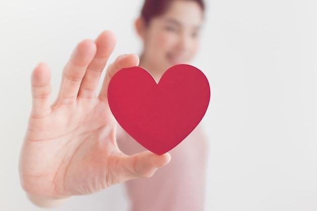 분홍색에서 여자는 사랑과 발렌타인의 개념에 심장 모양을 보여줍니다.