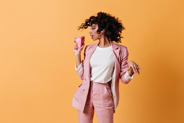 正面を保持しているピンクのスーツの女性