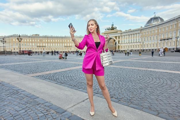 분홍색 정장을 입은 여성이 러시아 상트 페테르부르크의 역사적인 중심지를 배경으로 스마트 폰으로 셀카를 찍고 있습니다.